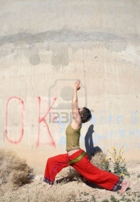 2586531-woman-in-the-yoga-pose-warrior-1-outdoors-near-a-large-industrial-wall-in-the-desert