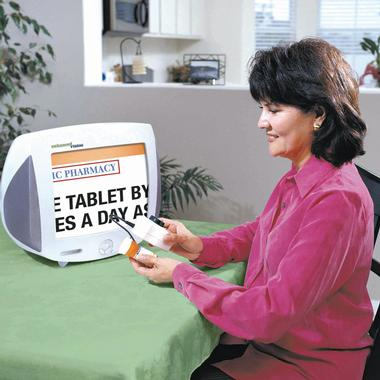Woman using the Max Digital 'Handeld' Magnifier to read the small print on a prescription pill container's label on a TV monitor