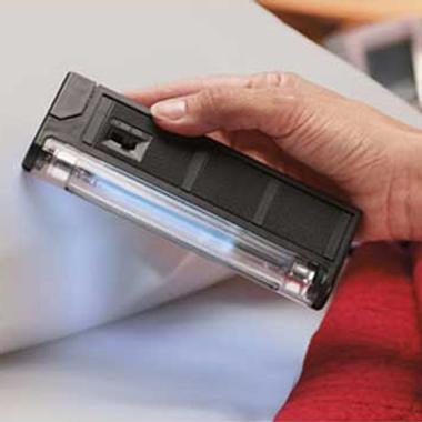 Personal Germ Eliminator, a handheld ultraviolet lamp, is used on a pillow and bed sheets