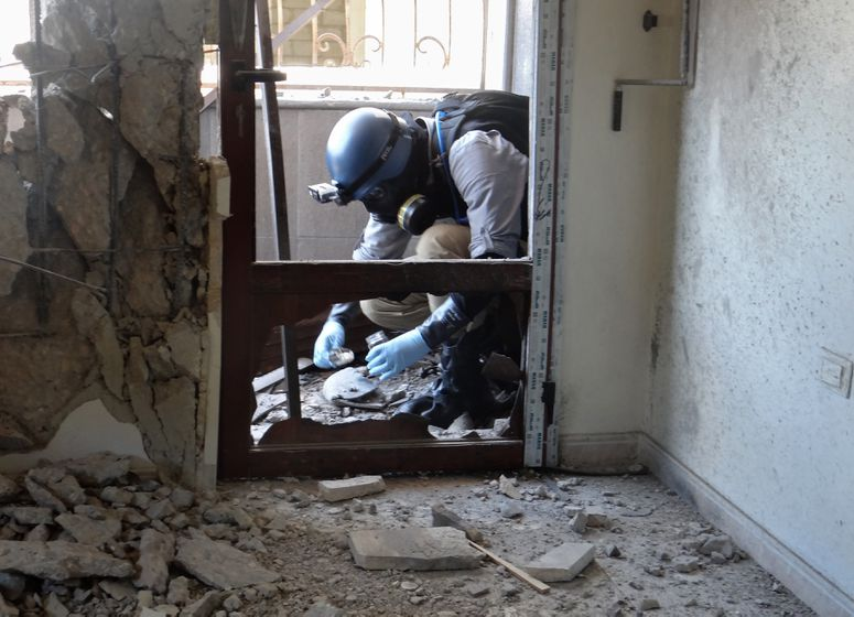 A UN chemical weapons inspector looks for signs of sarin in Ghouta, Syria (Ammar al-Arbini/AFP/Getty)
