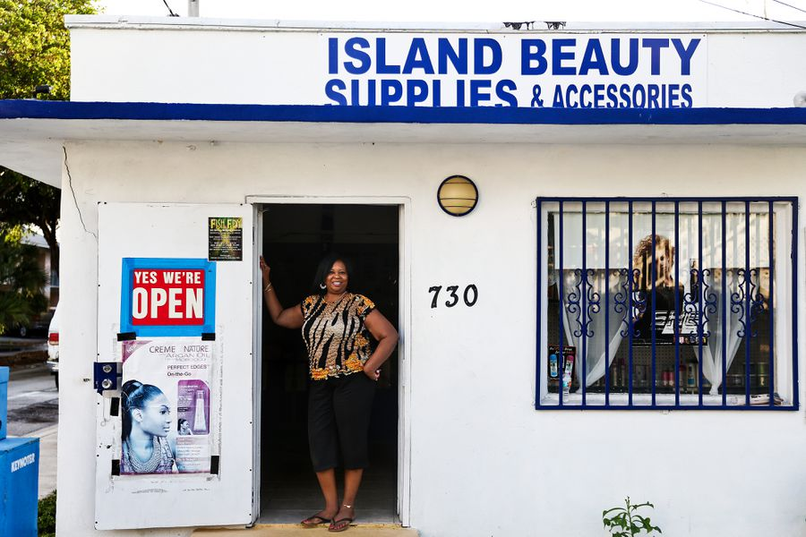 Sabrina Roberts standing in the doorway of her shop, Island Beauty Supplies.