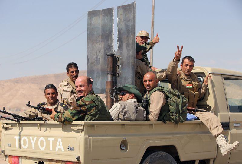 Peshmerga on the way to Mosul, celebrating military progress. AHMAD AL-RUBAYE/AFP/Getty Images