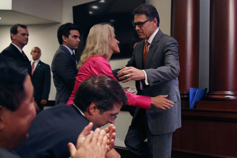 Republican strategist Kellyanne Conway reaches to hug former Texas Governor Rick Perry.