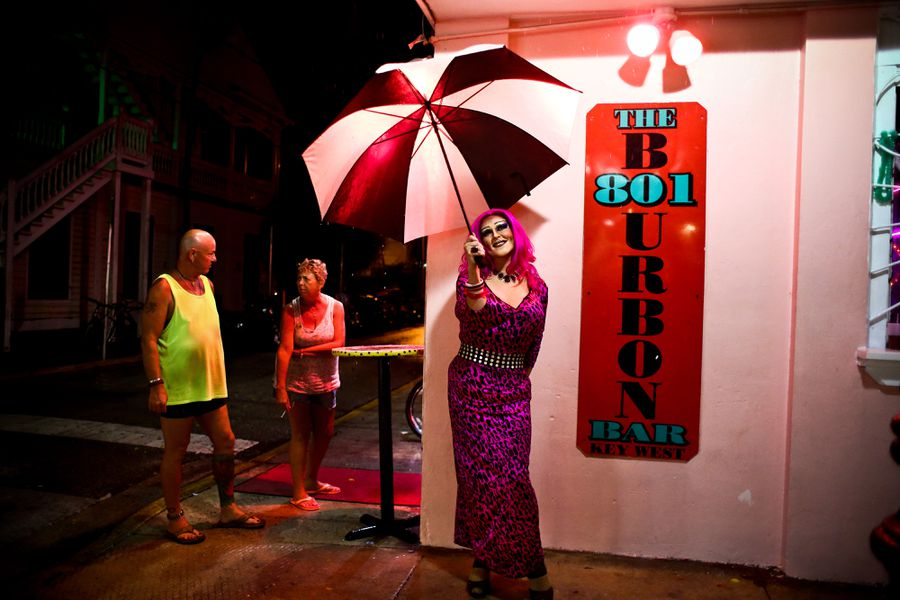 A drag queen outside of the sign for 801 Bourbon Bar.