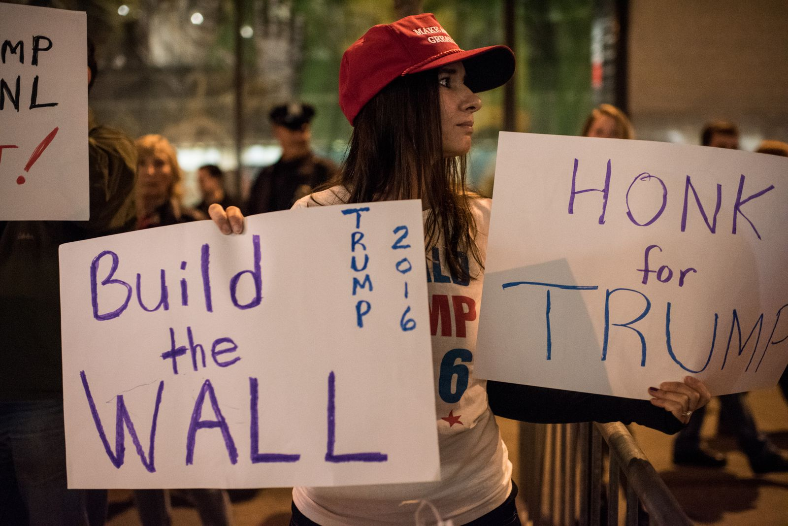 "A Trump supporter carries a sign saying ""Build the wall"""