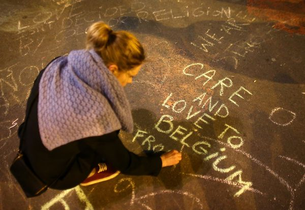 A woman writes a message on the ground as people leave tributes at the Place de la Bourse.