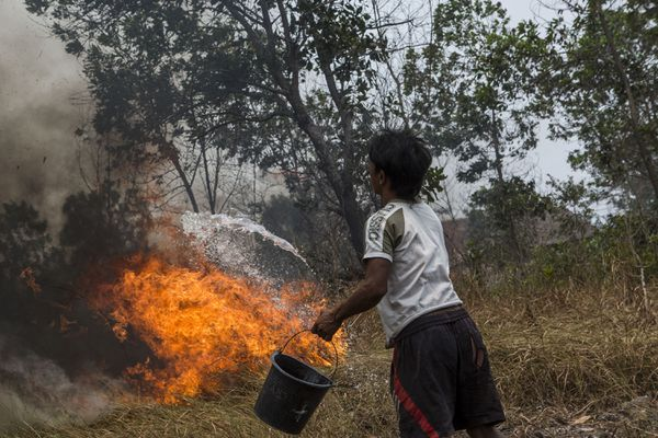 A man in Palembang, South Sumatra extinguishes a fire.