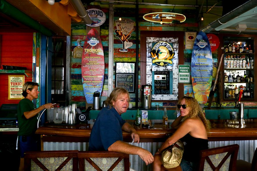 A man and a woman sitting at the bar at Blue Macaw Island Eats & Bar.