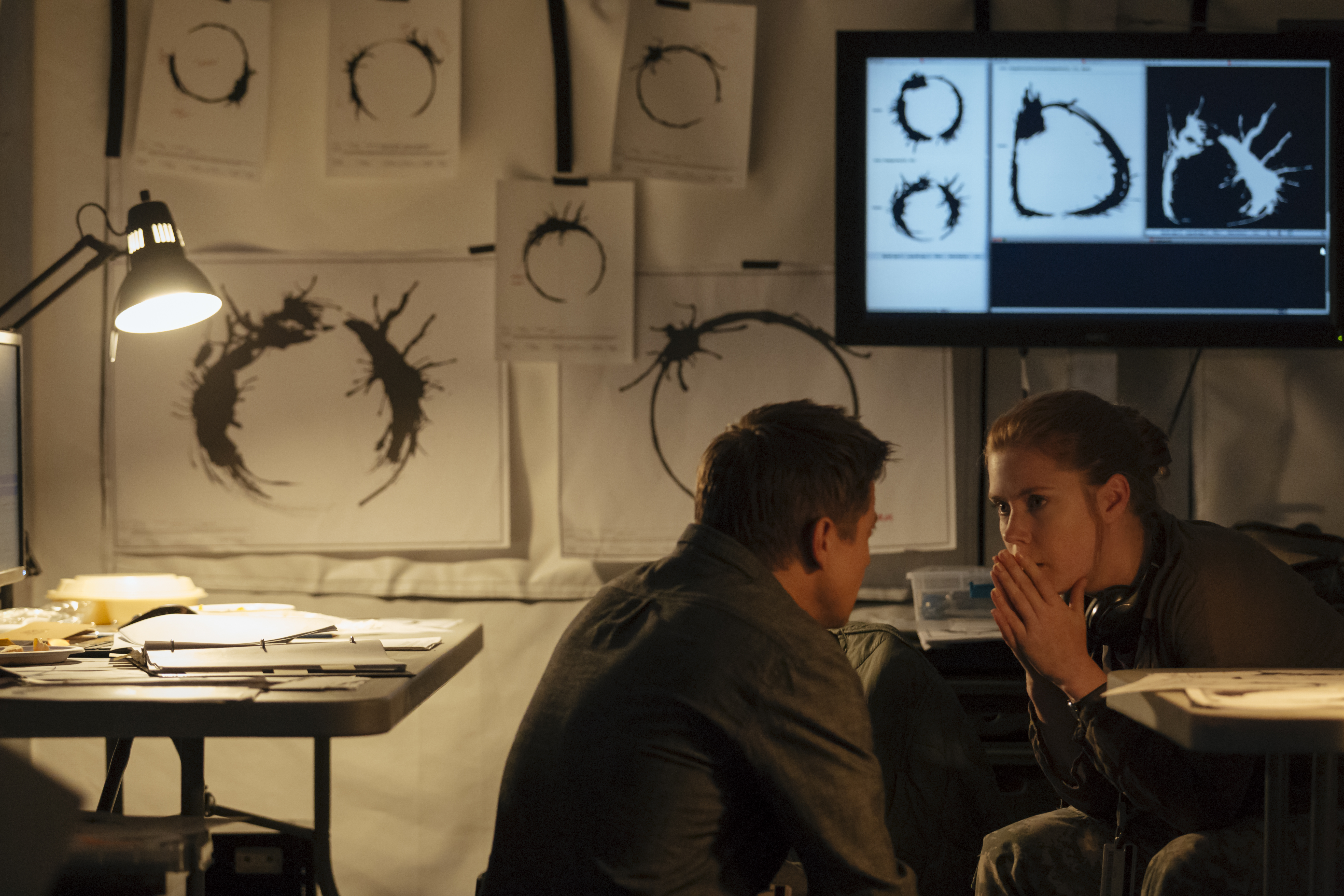 arrival spoilers let s discuss the hit movie s most divisive jeremy renner and amy adams surrounded by the alien language in arrival